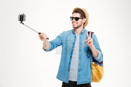 Cheerful man taking pictures with mobile phone and selfie stick