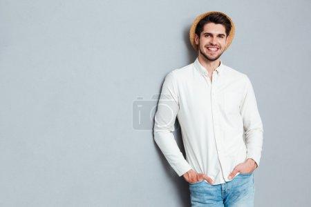 Photo pour Portrait d'un bel homme debout avec les bras dans des poches isolées sur un fond gris - image libre de droit