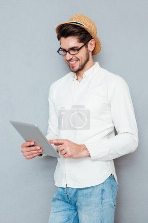 Portrait of a happy man in eyeglasses using tablet computer