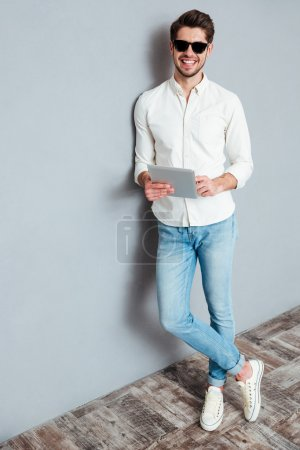 Photo for Full length portrait of a happy young man using tablet computer isolated on a gray background - Royalty Free Image