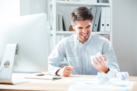 Photo pour Fou ennuyé jeune homme d'affaires travaillant et froisser le papier dans le bureau - image libre de droit