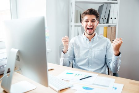 Cheerful excited young businessman celebrating success in office