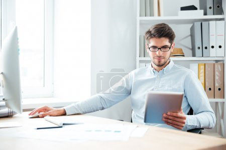 Young businessman sitting and using tablet computer in office