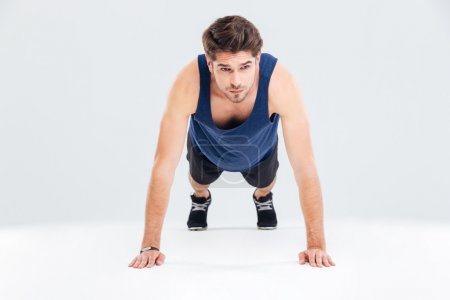 Handsome young man athlete training and doing plank exercise