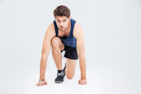 Photo for Attractive focused young sportsman ready to start running over white background - Royalty Free Image