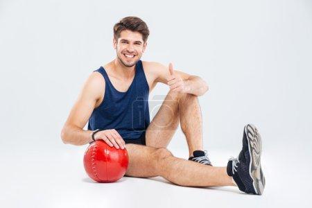 Photo pour Joyeux jeune sportif avec boule rouge assis et montrant les pouces vers le haut sur fond blanc - image libre de droit