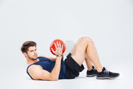 Attractive young sportsman holding red ball and doing crunches