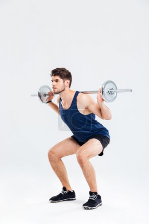 Handsome young man athlete doing squats with barbell