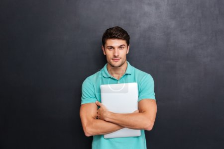 Photo for Serious confident young man standing and holding laptop over blackboard background - Royalty Free Image