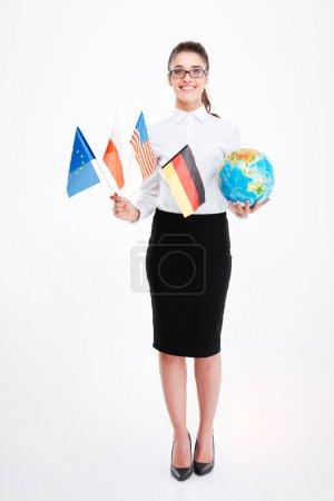 Photo for Full length of happy young businesswoman in glasses holding flags of several countries and earth globe over white background - Royalty Free Image