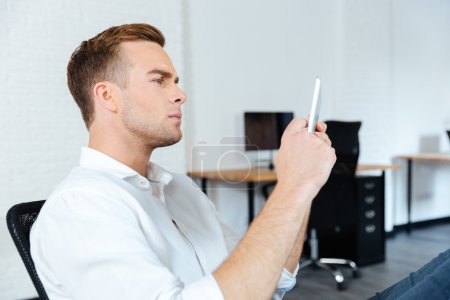 Serious conentrated young businessman sitting and using tablet