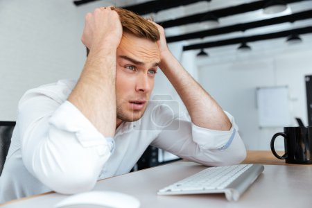 Photo for Upset disappointed young businessman sitting at workplace with hands on head - Royalty Free Image