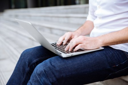 Photo for Closeup of young man sitting on stairs and using laptop - Royalty Free Image