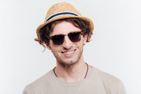 Closeup of cheerful young man in hat and sunglasses smiling