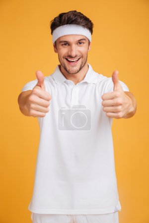 Cheerful handsome young sportsman showing thumbs up with both hands
