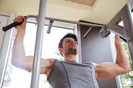 Fitness man doing exercises for arms muscles in gym