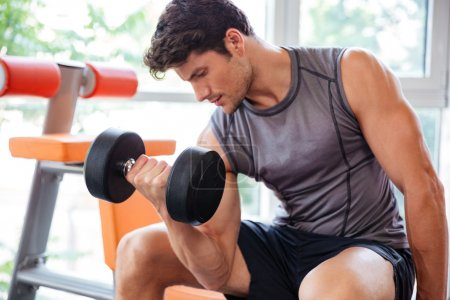 Fitness man working out with dumbbells in gym