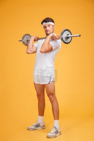 Playful young sportsman holding barbell and making funny face