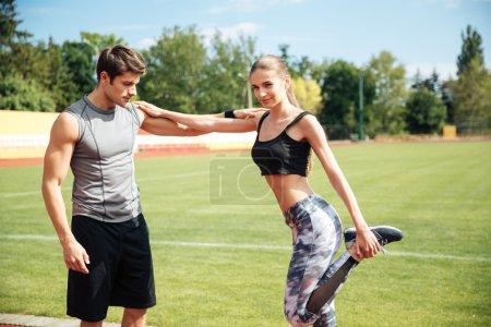 Photo pour Belle jeune athlète femme debout et étirant avec entraîneur personnel sur le stade - image libre de droit