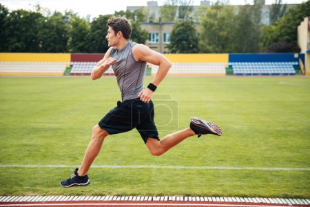 Side view of a sprinter running on athletics tracks