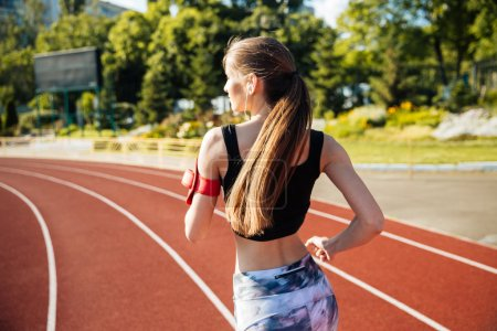 Back view of a female runner with mobile phone