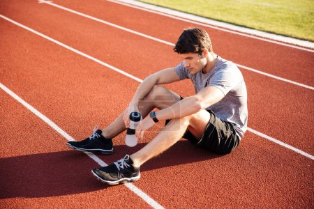 Young handsome man athlete resting with water bottle