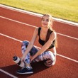 Fitness young woman sitting on running track and h...