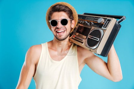 Happy young man in hat and sunglasses with boombox