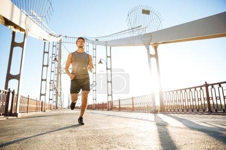 Photo for Handsome sports man running fast along big modern bridge at sunset light - Royalty Free Image