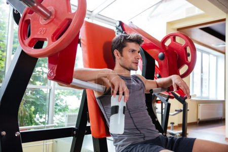 Portrait of a fitness man resting on bench at gym