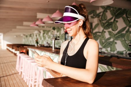 Sports woman listens music with earphones and smartphone in cafe
