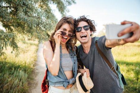 Photo pour Jeune sourire heureux couple joyeux w randonnée dans la forêt et faire selfie - image libre de droit