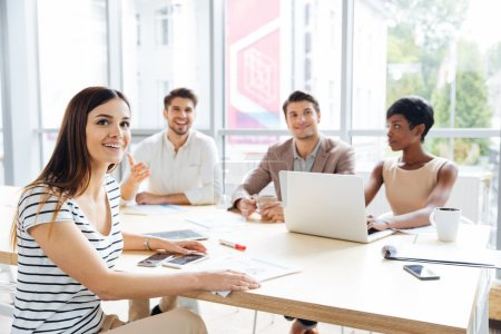 Photo for Group of smiling young business people using laptop and listening presentation in office - Royalty Free Image