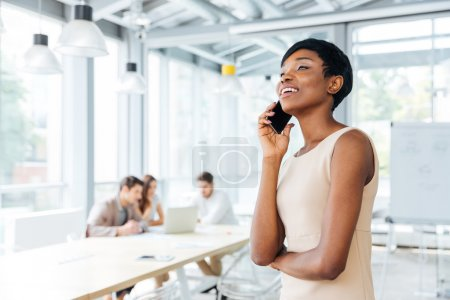 Cheerful businesswoman standing and talking on mobile phone in office