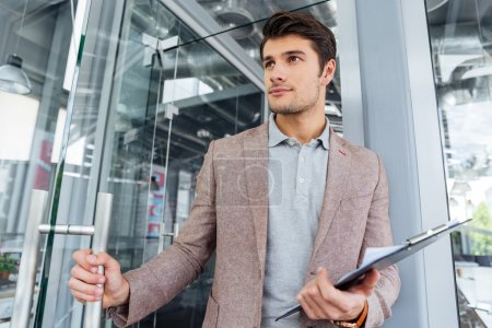 Businessman holding clipboard and entering the door in office