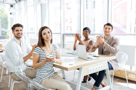 Happy young business people applauding at meeting in office
