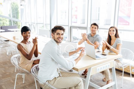 Business people sitting and clapping hands during presentation in office