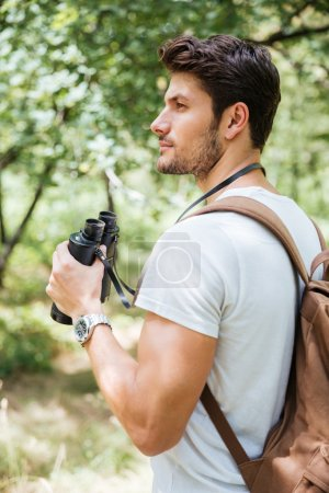 Pensive young man with backpack holding binoculars in forest