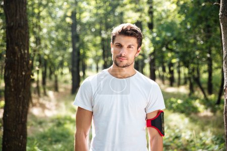 Photo for Portrait of handsome young man athlete with handband in forest - Royalty Free Image