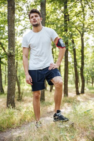 Sportsman with mobile phone in handband standing in forest