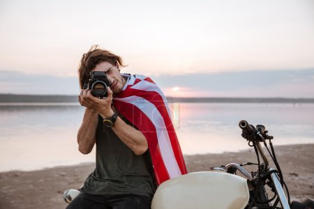 Man making photo with camera while sitting on his motocycle