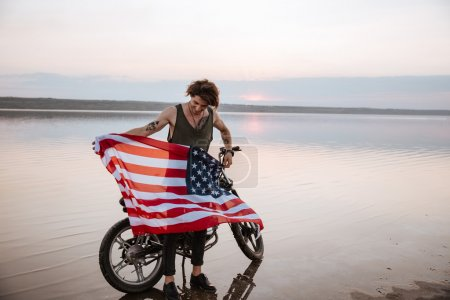 Man holding american flag at the desert standing near motorcycle