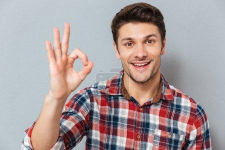 Photo pour Portrait d'un homme heureux montrant un geste correct sur fond gris - image libre de droit