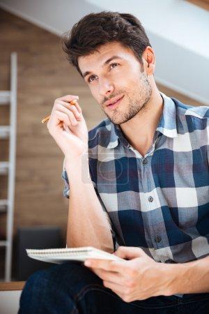 Photo pour Jeune homme pensif en chemise à carreaux écrivant dans un bloc-notes et pensant à la maison - image libre de droit