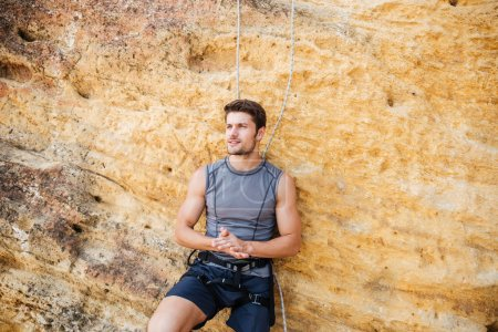 Young handsome sportsman getting ready to climb a cliff