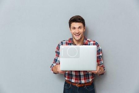 Photo pour Joyeux jeune homme en chemise à carreaux debout et tenant un ordinateur portable sur fond gris - image libre de droit