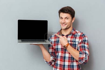 Photo for Happy young man in plaid shirt pointing on blank screen laptop over grey background - Royalty Free Image
