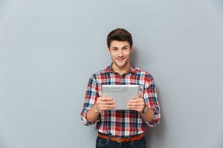 Photo pour Jeune homme attrayant et souriant en chemise à carreaux utilisant une tablette sur fond gris - image libre de droit