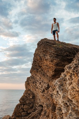Young sportsman standing on the mountain rock by the sea