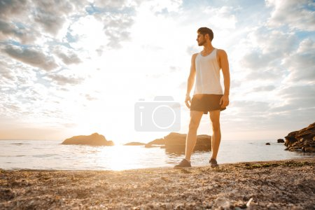 Man athlete standing with arms raised and looking at sunset
